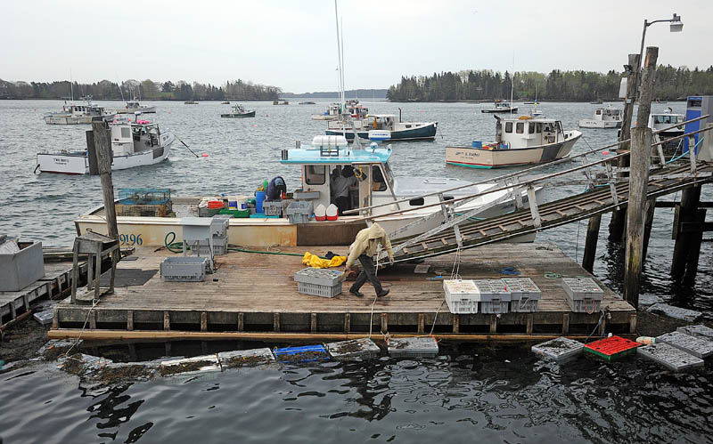 Craig Mott, 36, center, the dock manager at the Friendship Lobster Co-Op, helps unload the day's lobster haul from the Miss Kylie in Friendship Harbor on Wednesday.