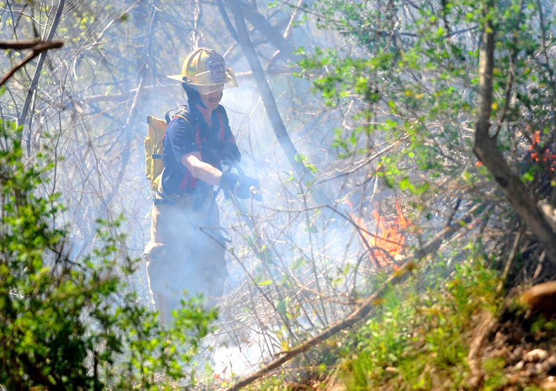 Capt. Kevin Fredette of the Winslow Fire Department battles a blaze in the hills behind Dallaire Street, near the Kennebec River, in Winslow Saturday afternoon.