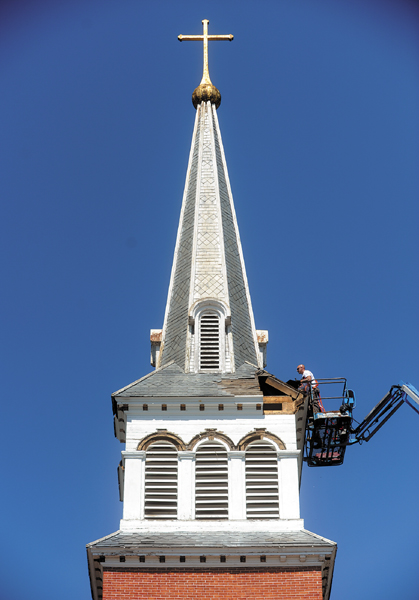 Workers from Corpus Christi Parish in Waterville prepare the steeple for removal during the demolition of St. Francis de Sales on Thursday.