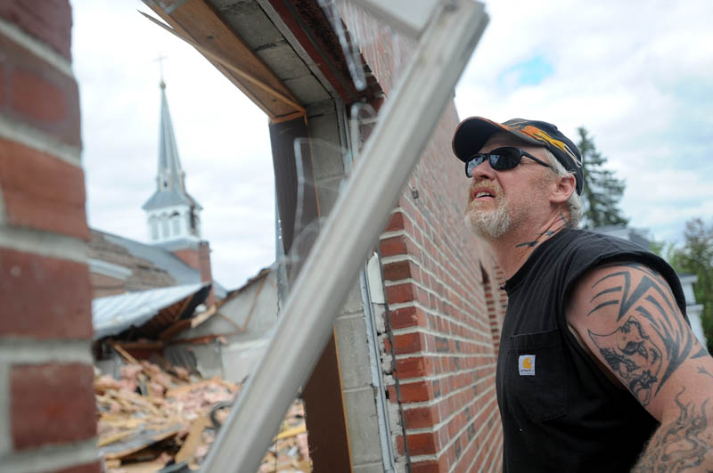 Kip Walker, a heavy machine operator for Danley Demolition, Inc., tears off a wood sill during demolition of St. Francis de Sales Catholic Church, its rectory and its parish hall, on Elm Street in downtown Waterville on Tuesday.