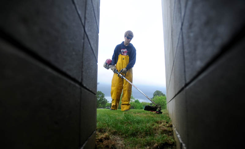 Cameron Mills, 21, of the Colby College grounds crew, whacks weeds in his rain slickers as rain falls in Waterville Friday afternoon.