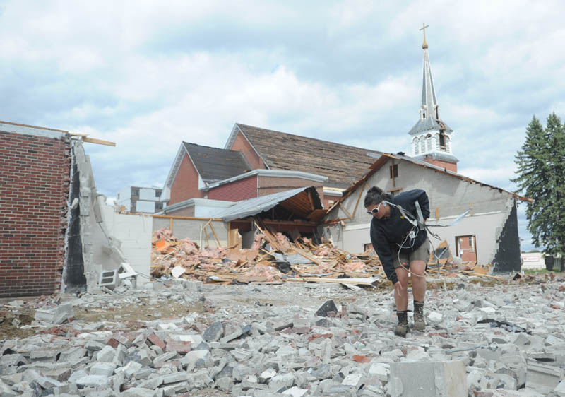 Gina Surrette, of Danley Demolition, Inc., picks metal pieces from crushed concrete during the demolition of St. Francis de Sales Catholic Church, its rectory and its parish hall, on Elm Street in downtown Waterville on Tuesday.