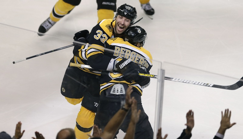 Boston Bruins center Patrice Bergeron (37) is embraced by teammate Zdeno Chara (33) after scoring the game winning goal off Toronto Maple Leafs goalie James Reimer during overtime in Game 7 of their NHL hockey Stanley Cup playoff series in Boston, Monday, May 13, 2013. The Bruins won 5-4. (AP Photo/Charles Krupa)