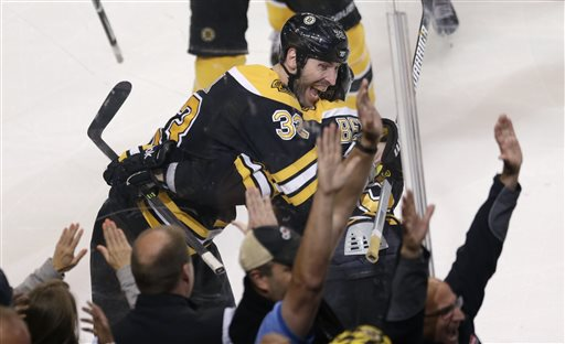 Boston Bruins center Patrice Bergeron, right, is embraced by teammate Zdeno Chara, left, after scoring the game winning goal off Toronto Maple Leafs goalie James Reimer during overtime in Game 7 of their NHL hockey Stanley Cup playoff series in Boston, Monday, May 13, 2013. The Bruins won 5-4. (AP Photo/Charles Krupa)
