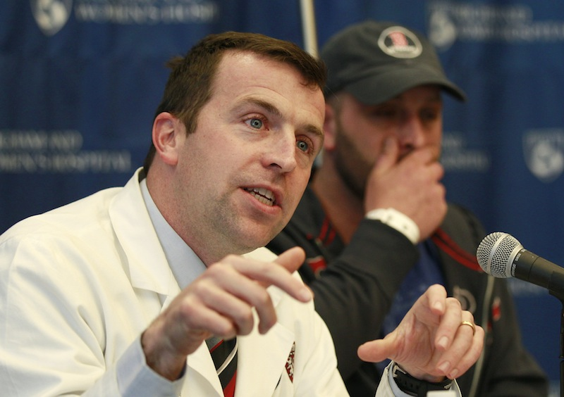 Surgeon Dr. Robert Riviello, left, describes injuries sustained by Boston Marathon explosion survivor Jarrod Clowery, of Stoneham, Mass., right, during a news conference at Brigham and Women's Hospital in Boston, Mass., Tuesday, April 30, 2013. Clowery suffered severe burn and shrapnel wounds in the bombings that killed three people and wounded more than 260 others. (AP Photo/Charles Krupa)