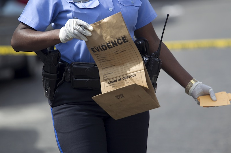 New Orleans police officer collects evidence at the scene of a shooting at the intersection Frenchman Street at N. Villere on Mother's Day in New Orleans, Sunday May 12, 2013. Gunmen opened fire on dozens of people marching in a Mother's Day neighborhood parade in New Orleans on Sunday, wounding at least 17, police said. (AP Photo/Doug Parker) New Orleans Police;Shooting