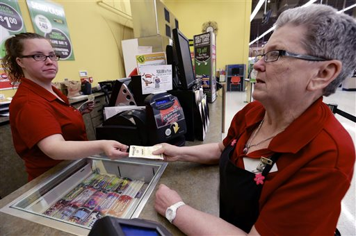 Sharon Brickey, right, purchases a Powerball ticket from Tiffany Enders, left, at a Baker's supermarket in Omaha, Neb., on Wednesday. Enders recently sold a million dollar Powerball ticket at the store.
