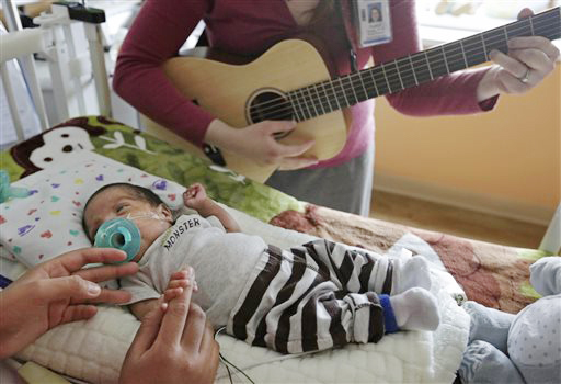 Music therapist Elizabeth Klinger, right, plays guitar and sings for Augustin as he grips the hand of his mother, Lucy Morales, in the newborn intensive care unit at Ann & Robert H. Lurie Children's Hospital in Chicago recently.