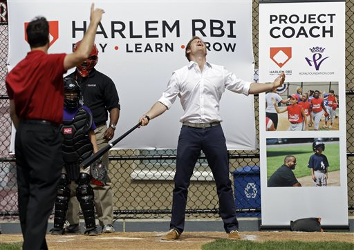 Prince Harry reacts after hitting a baseball pitched to him by New York Yankees' Mark Teixeira, left, during a visit to the Harlem RBI youth sports and school program in New York on Tuesday.