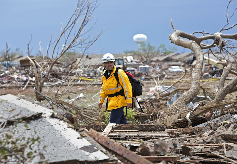 A rescue worker checks the rubble in a residential area in Moore, Oklahoma May 21, 2013 after a massive tornado struck the area May 20. Emergency workers pulled more than 100 survivors from the rubble of homes, schools and a hospital in an Oklahoma town hit by a powerful tornado May 20, and officials lowered the death toll from the storm to 24, including nine children. (REUTERS/Richard Rowe)