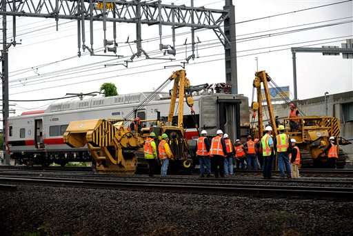 A derailed Metro-North rail car is hoisted back on to the tracks in Bridgeport. Conn. on Sunday. Crews will spend days rebuilding 2,000 feet of track, overhead wires and signals following the collision between two trains Friday evening that injured 72 people,
