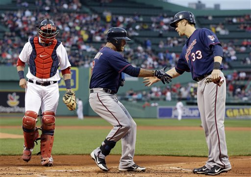 Minnesota Twins designated hitter Ryan Doumit is greeted at the plate by Justin Morneau (33) after his two-run home run as Boston Red Sox catcher Jarrod Saltalamacchia walks back to position during the first inning of a baseball game at Fenway Park in Boston, Wednesday, May 8, 2013. (AP Photo/Elise Amendola) Fenway Park