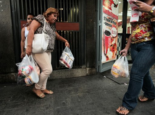 A customer leaves a private super market in Caracas, Venezuela, with her purchases, including toilet paper, on Wednesday.