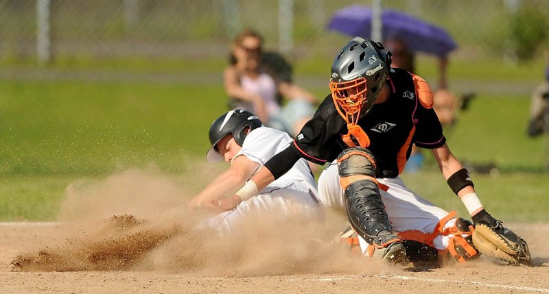 SAFE: Waterville Senior High School's Racean Wood, left, slides by Winslow High School catcher Bobby Chenard for a run in the fifth inning of the Kennebec Valley Athletic COnference Class B championship game in Winslow on Friday. Waterville defeated Winslow 10-0 in six innings.