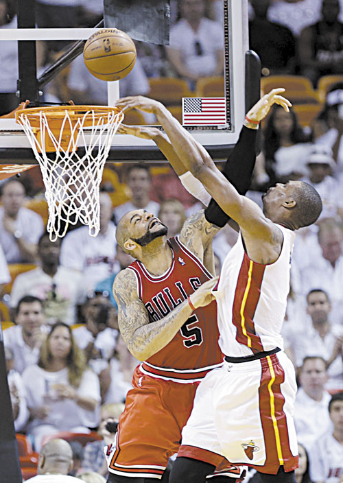 EVEN AS CAN BE: Miami Heat center Chris Bosh, right, is fouled by Chicago Bulls forward Carlos Boozer (5) as he goes up for a shot during Game 2 of their Eastern Conference semifinal Wednesday in Miami.