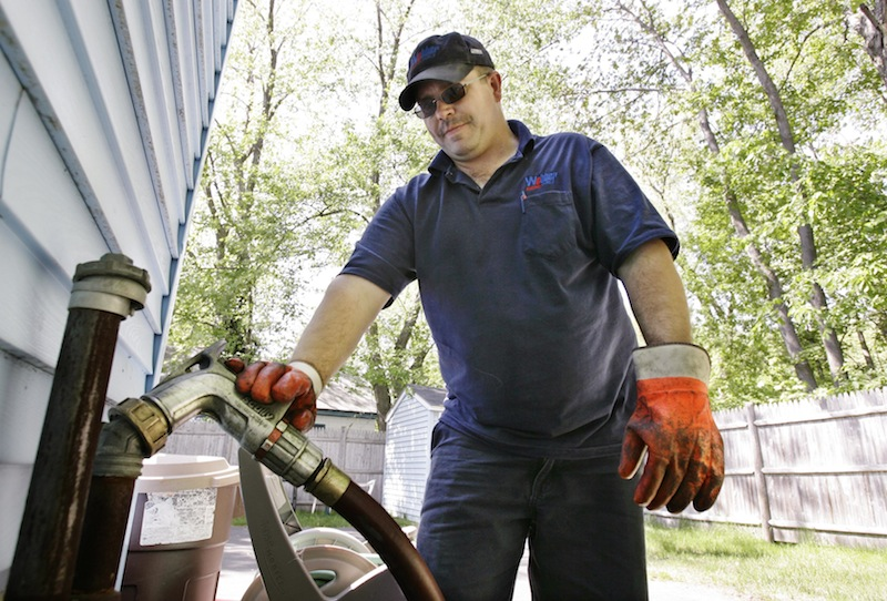 In this May 2008 file photo, Tim Weeks makes a home heating oil delivery in Portland, Maine. A legislative panel voted 12-1 Friday, May 24, 2013 to endorse an ambitious package of proposals aimed at lowering Maine's high electricity and heating costs. (AP Photo/Joel Page)