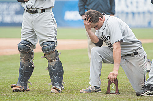 TOUGH DAY: University of Southern Maine's Troy Thibodeau leans down on the trophy during the postgame ceremony after the championship game against Linfield on Tuesday at Time Warner Cable Field in Appleton, Wis. The Huskies lost 4-1.