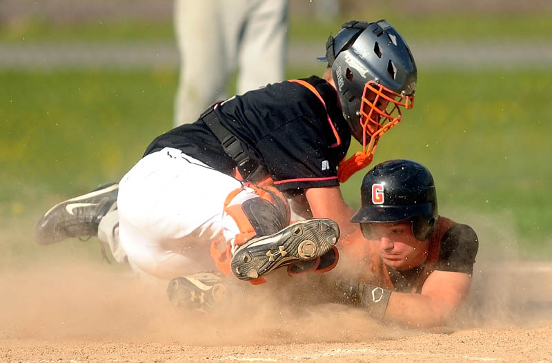 Winslow High School catcher Bobby Chenard, left, tags out Gardiner High School's Frank Chepke on a steal attempt in the fifth inning Wednesday at Winslow High School. The Black Raiders defeated the Tigers 1-0.