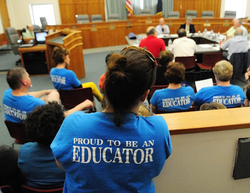 Several people wearing blue Augusta Education Association T-shirts attend a standing room only city council budget wrap-up meeting on Thursday in Augusta City Center.