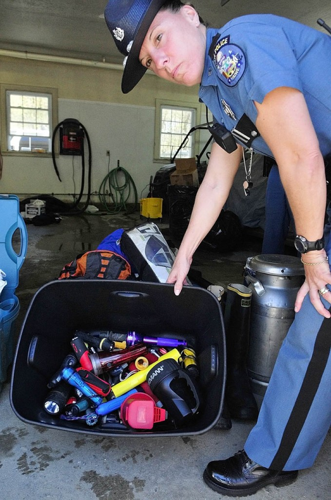 Trooper Diane Perkins-Vance shows a bin of flashlights recovered from the campsite of the North Pond Hermit, Christopher Knight, during an event at the Maine State Police Troop C barracks on Saturday in Skowhegan.