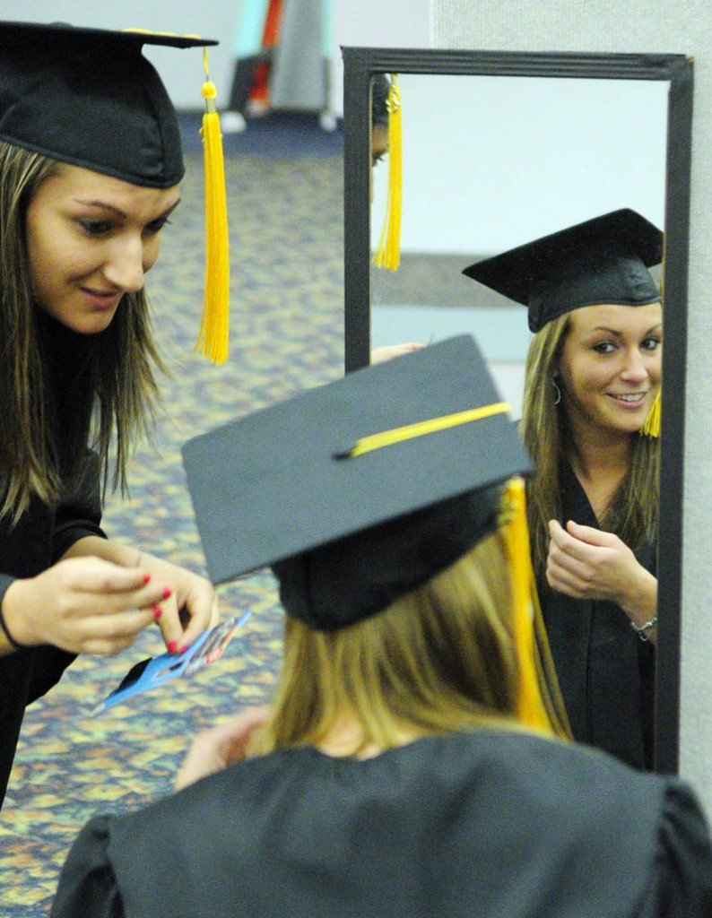 Brittany Bouchard, left, of Waterville, helps classmate Chelsi Brewer, of Skowhegan, adjust her mortarboard before the Kennebec Valley Community College commencement on Saturday at the Augusta Civic Center.