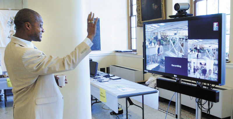 Rep. Craig Hickman, D-Winthrop, waves through a video conferencing monitor to Maine State Library employee Jill Sampson, who was watching an event in the State House's Hall of Flags, held to celebrate the completion of the Maine State Library's $1.9 million Broadband Technology Opportunity Program, on Friday.
