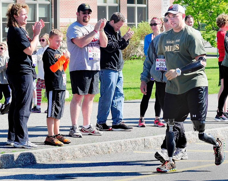 Spectators clap for Staff Sgt. Travis Mills as he heads to the finish line at the second annual Miles For Mills 5k on Monday at Cony High School in Augusta. Mills walked part of the course.