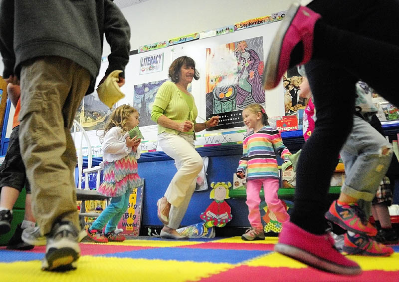 "Teacher Karen Toothaker, center, leads her students as the sing and dance along to a recording of ""The Bean Bag Alphabet Rag"" during a pre-kindergarten class at Manchester Elementary School in this 2014 file photo."