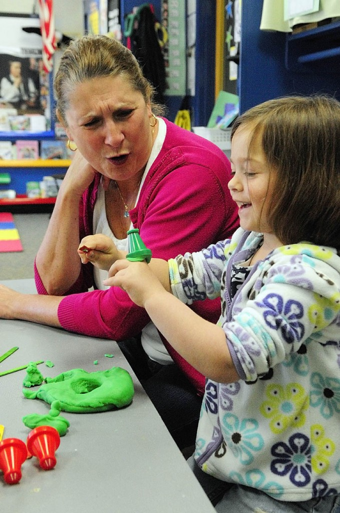 Ed Teck Deb Noyes, left, talks to student Olivia Hall as they play with Play-Doh recently during a pre-kindergarten class at Manchester Elementary School.