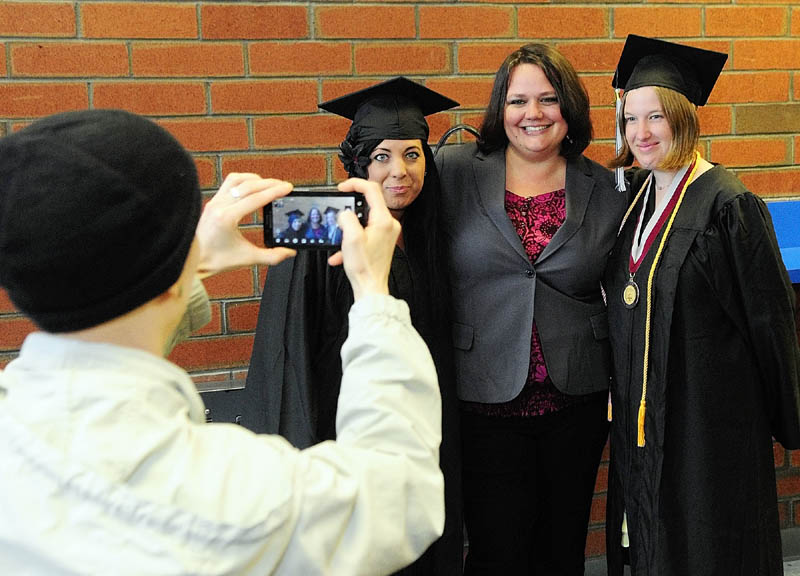 Emily Naples, left, snaps a camera phone photo of Rillyria Sherifi, Tessa Pyles and Tessa Hayes before the University of Maine at Augusta graduation on Saturday at the Augusta Civic Center.
