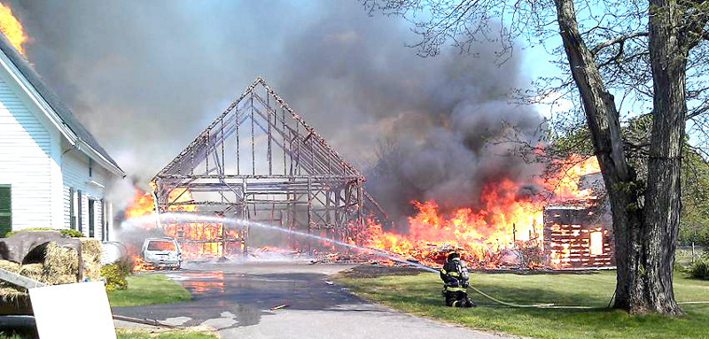 Firefighters battle a fire on the Hallowell-Litchfield Road in Litchfield on Friday.