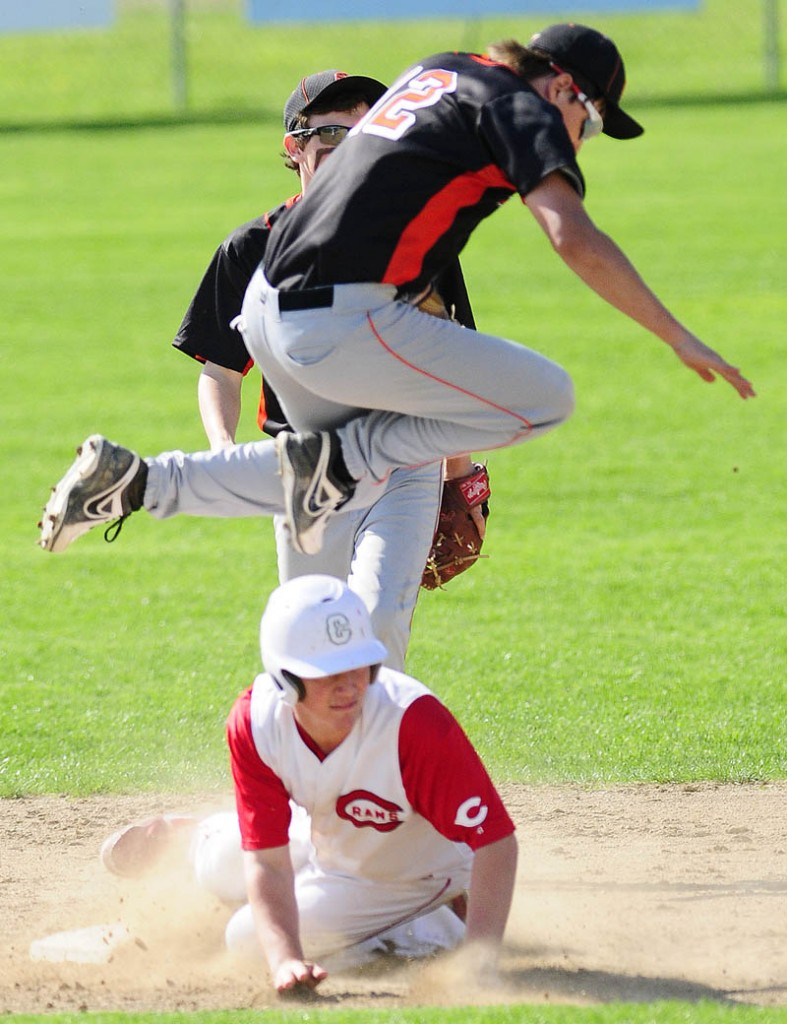 Staff photo by Joe Phelan Skowhegan shortstop Kameron Nelson leaps out of way of sliding Cony baserunner Mitchell Caron during a game on Friday May, 10 2013 in Augusta.
