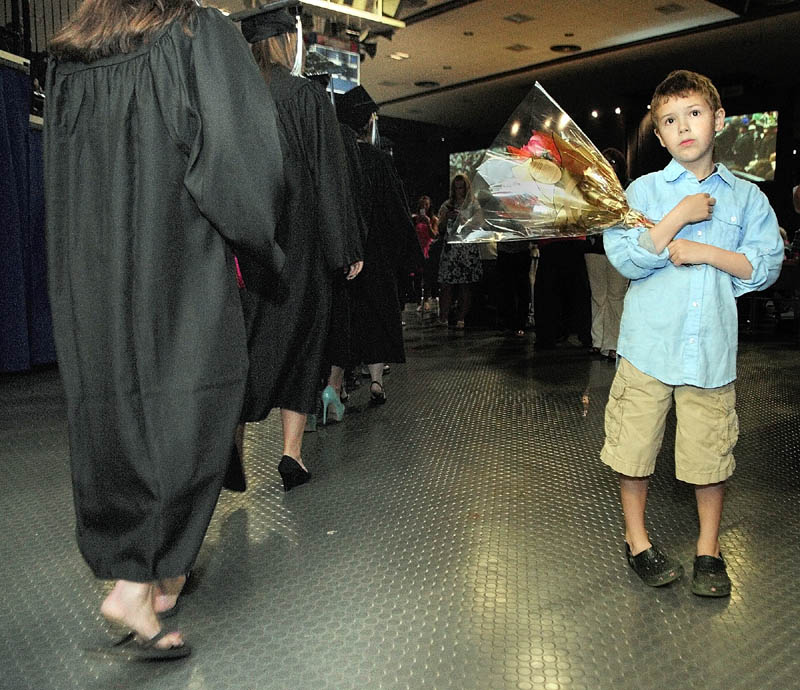 As a line of graduates passes, John Rice, 7 of Damariscotta, looks for his mother Susanna Norwood-Burns to give her a bouquet at the start of University of Maine at Augusta graduation.