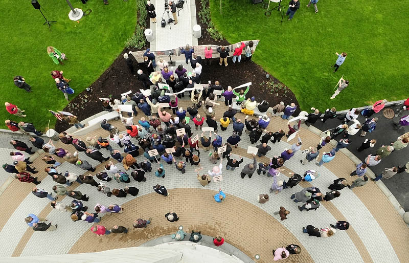 People chant at the start of a lunchtime rally to protest Gov. Paul LePage's budget plan on Wednesday, on the plaza outside west entrance of the State House in Augusta. Speakers included Hallowell Mayor Charlotte Warren; Leslie Manning, a board member of the Maine Council of Churches; and Ron Green, president of the Bangor Professional Firefighters. The governor's office is located near the rally site.