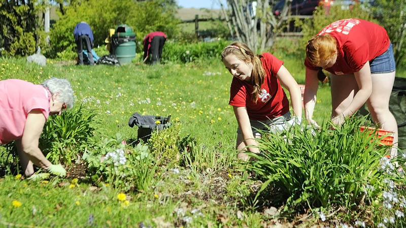 Nancy Voisine, left, and Cony High students Christina Claudel and Rebecca Coniff clean up a flower bed on Thursday at the Kennebec Valley Garden Club park in Augusta.