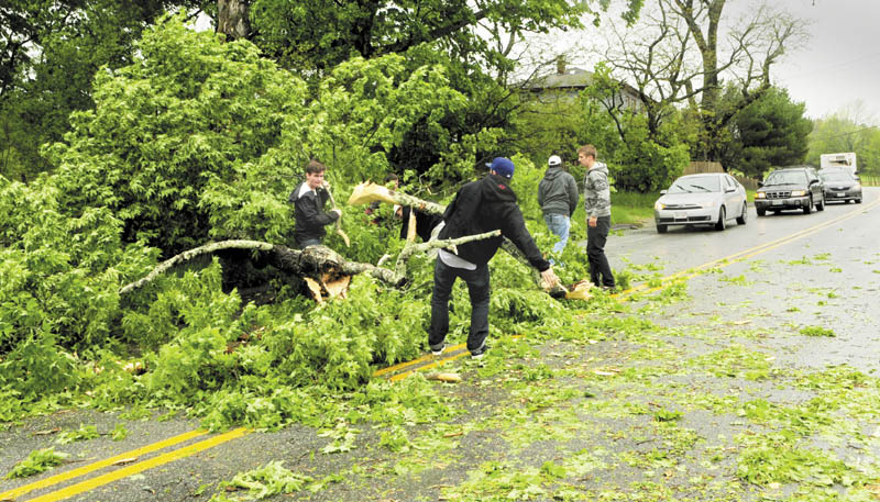 Several men got out of their cars clear a fallen tree from the westbound lane of Route 17 on Saturday in Readfield. The group, who said they were Kents Hill School alumni enroute to graduation there, removed what limbs and branches they could by hand. That cleared the view of the road so drivers could see if oncoming traffic. Shortly after that, two other men with chainsaws removed the trunk.