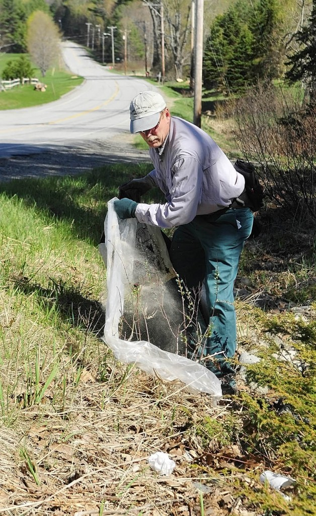 Gary Hinkley picks up trash along Route 17 on Saturday in Manchester. He was part of the Manchester Conservation Commission's annual roadside cleanup event. More than 40 people helped to pull trash, tires, and recyclables off the roadsides. Boy Scouts Troop 622, Cub Scout Pack 622 and the Hope Baptist Church were involved in the event.