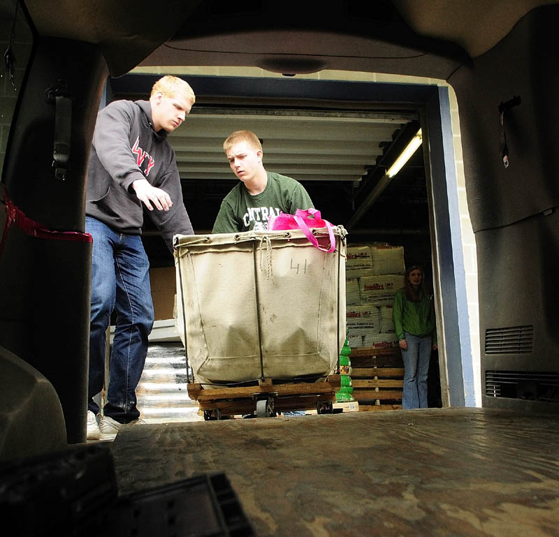 "Sam Birch, left, and Joe Wathen roll a mail cart full of donated food into the Augusta Food Bank storage area on Saturday as part of the annual National Association of Letter Carriers' Stamp Out Hunger Food Drive. ""It's one of our biggest drives of the year and fills up storage area and shelves at time of year people don't traditionally think of hunger issues,"" said Abbie Perry, executive director of the Augusta Food Bank. The group's next big event will be a lawn sale, food drive and hot dog sale on June 1 at the Shaw's store on Western Avenue in Augusta."
