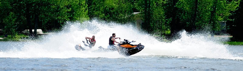 Christopher Carron, left, of Vassalboro, and Josh Dyer, of Benton, take a spin on their personal water crafts on Thursday in China Lake in China. It was a warm and sunny day, but the water was still cold.