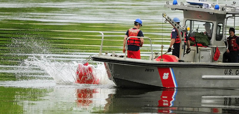 Coast Guardsmen drop a bouy into the Kennebec River on Wednesday between Chelsea and Hallowell.