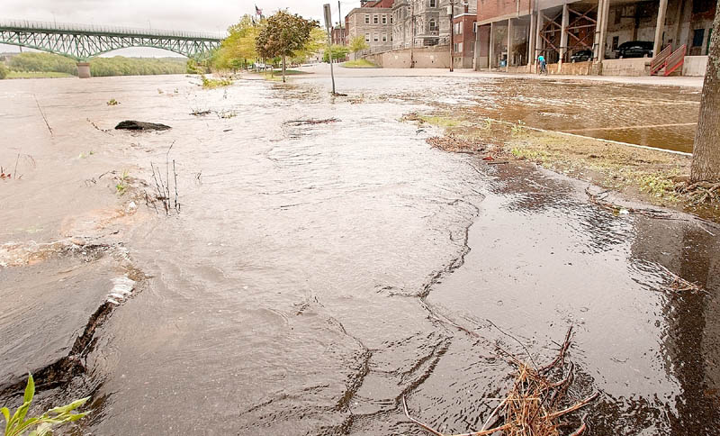 The Kennebec River laps over its banks across sidewalk and parking lot in downtown Augusta on Sunday afternoon.
