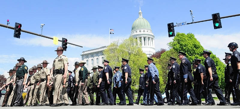 Law enforcement officers march around the corner from Union Street onto to State Street on their way to the Law Enforcement Memorial during a ceremony on Thursday near the State House in Augusta. Attorney General Janet Mills was the keynote speaker for the 23rd annual event, which focus' on the granite plaques with the names of the officers who have killed in the line of duty. There were no new names to be added this year.