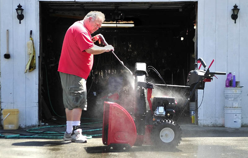 Roger Badershall power washes a snowblower on Tuesday in Augusta. He joked that it was probably safe to put it away for the season now.