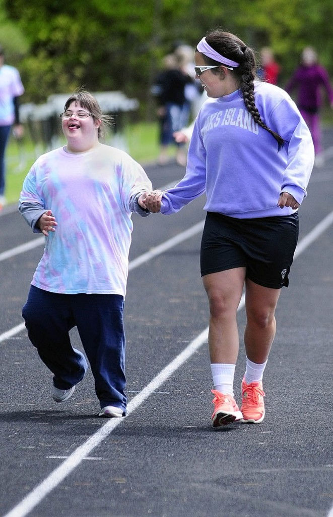 Messalonskee athlete Caitlin Douin and volunteer Natalie Hunt run the 100 meters event during the Kennebec Area Special Olympics Games on Tuesday at Hall-Dale High School in Farmingdale.