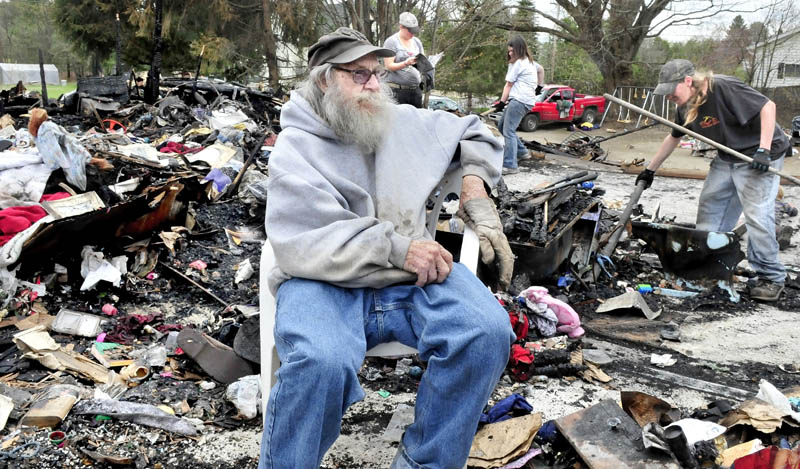 Clyde Berry on Thursday speaks about the offers of help he has received amid the rubble of his home in Benton that was destroyed by fire Monday. Looking for salvageable items in background are Barbara Berry, left, Jayme Sabins and Derrick Berry.