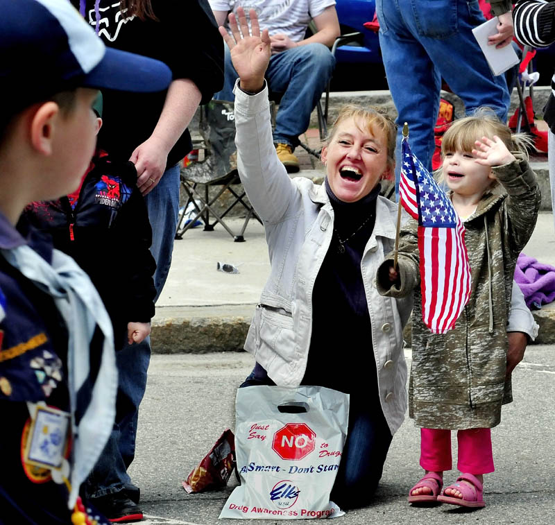 Kimberly Brooks and her niece, Mackenzie Gifford ,wave hands and flags at Memorial Day parade participants in Waterville on Monday.