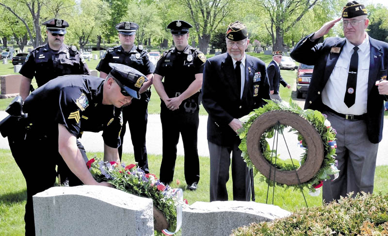 Waterville police Sgt. Lincoln Ryder lays a wreath for fallen law enforcement officers during a wreath-laying ceremony for veterans, firefighters, police and emergency workers on Sunday at the St. Francis and Pine Grove cemeteries in Wateville.