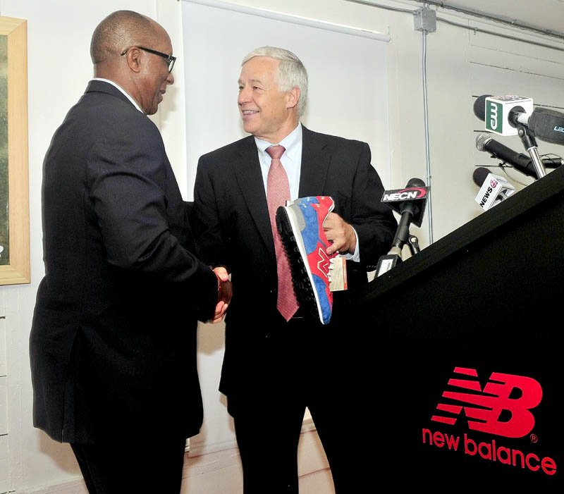 U.S. Rep. Mike Michaud, right, gives U.S. Trade Representative Ambassador Ron Kirk a pair of New Balance shoe company sneakers on behalf of the company during a tour of the facility in Norridgewock on Sept. 13.