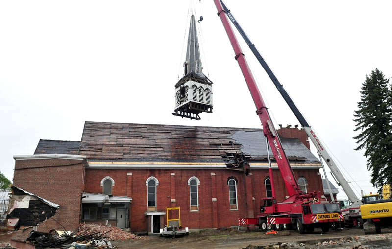 The W. H. Green & Sons crane company brought in a second crane to successfully remove the steeple from the St. Francis de Sales Catholic Church in Waterville on Wednesday. The church will be torn down for a housing project.