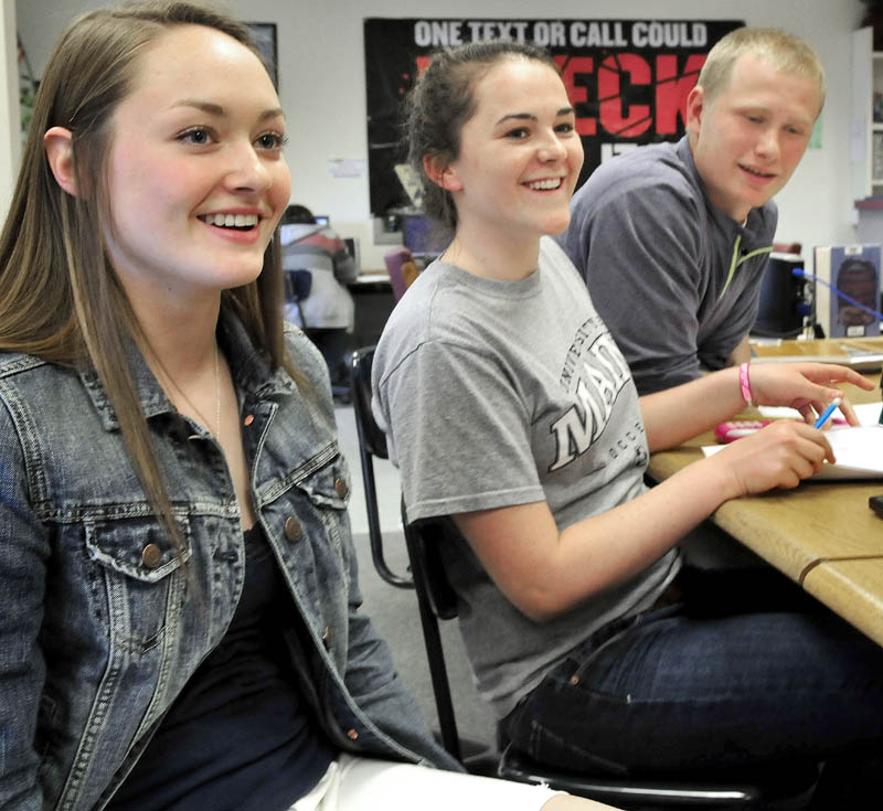 Erskine Academy students react happily to hearing the school received a grade B by the State Department of Education on Wednesday. From left are Taylor Bailey, Abigail Glidden and Jared Gartley.